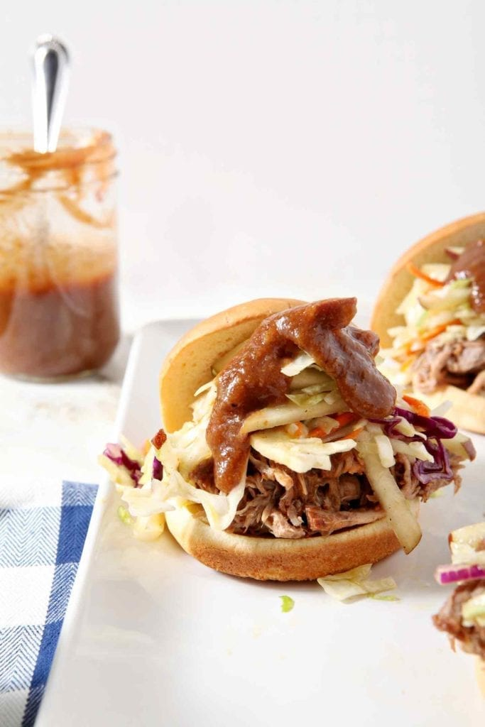 Three Pear BBQ Pulled Pork Sandwiches with Pear Slaw sit on a white platter with a BBQ sauce jar in the background