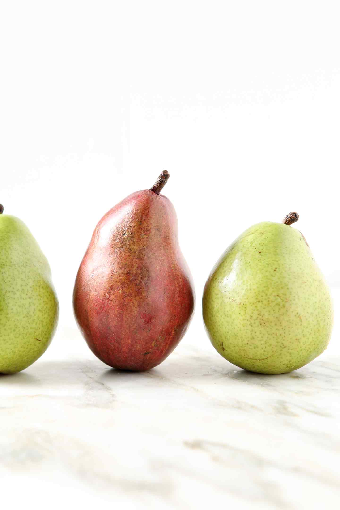 Three pears are lined up on a marble background