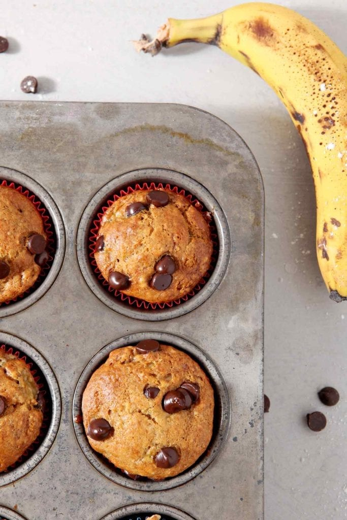Vegan Banana Chocolate Chip Muffins, fresh from the oven, remain in the muffin tin, surrounded by chocolate chips and bananas