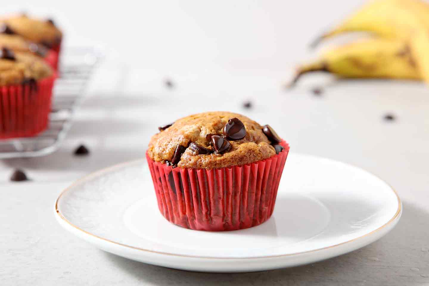A lone Vegan Banana Chocolate Chip Muffin is placed on a white plate for serving