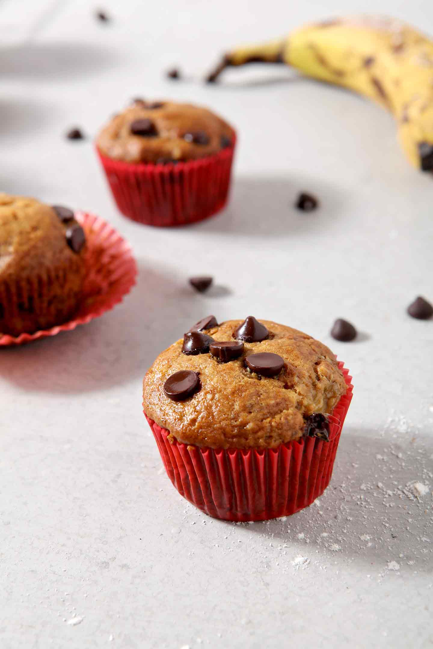 Three Vegan Banana Chocolate Chip Muffins sit on a grey background, surrounded by chocolate chips and bananas