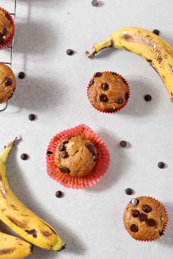 Overhead image of Vegan Banana Chocolate Chip Muffins, on a grey background, surrounded by chocolate chips and bananas