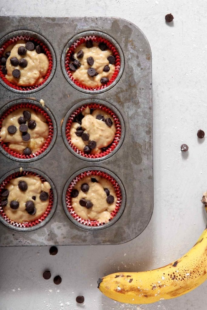 Vegan Banana Chocolate Chip Muffins sit in a muffin tin before baking.