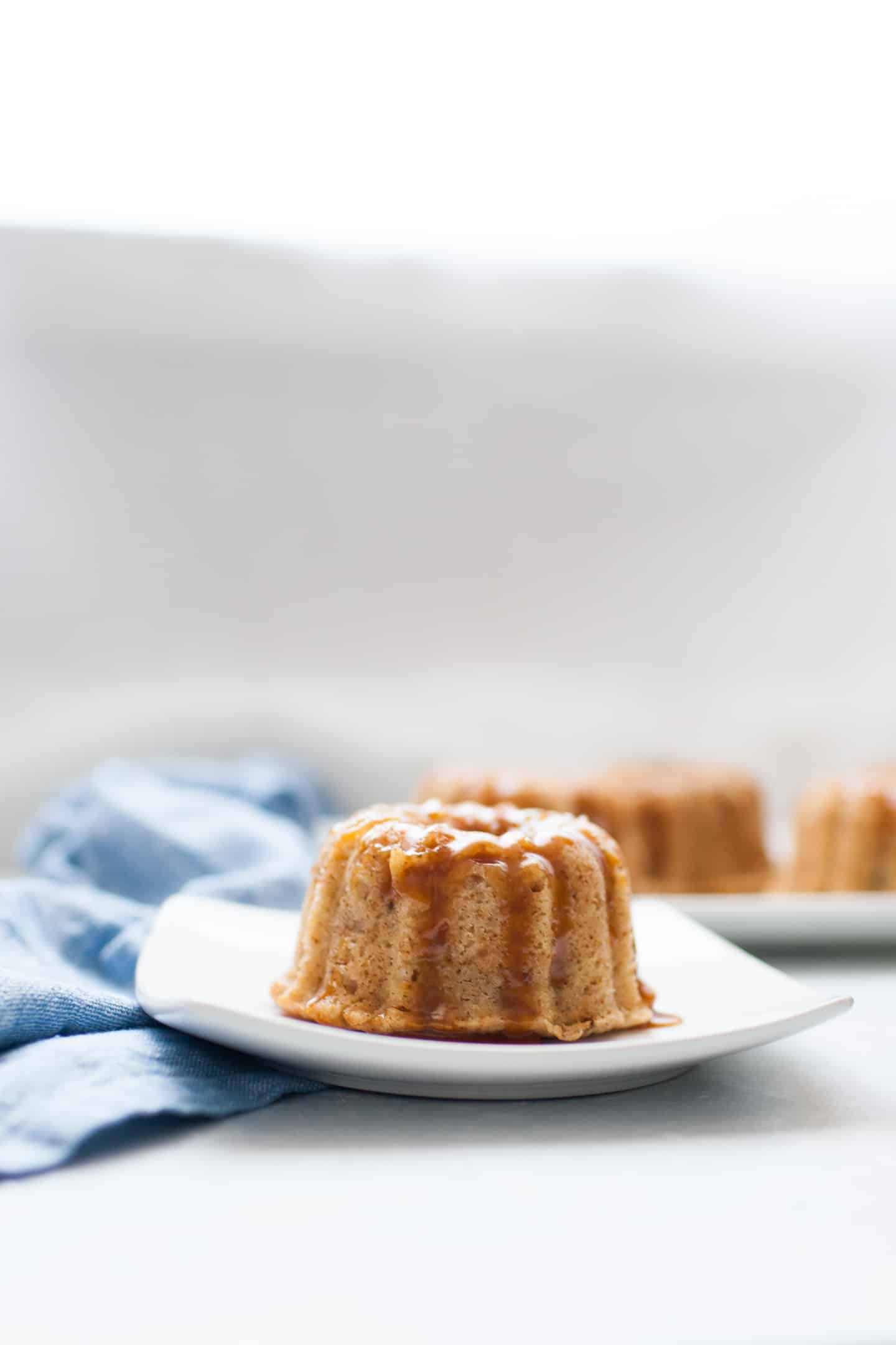 Mini bundt shaped cakes sitting on a white serving platter with small jar of caramel in the background.