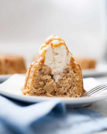 Mini spice cake that has had a bite taken out of it with a fork. Shows the inside of the cake with a scoop of ice cream and caramel drizzled on it.