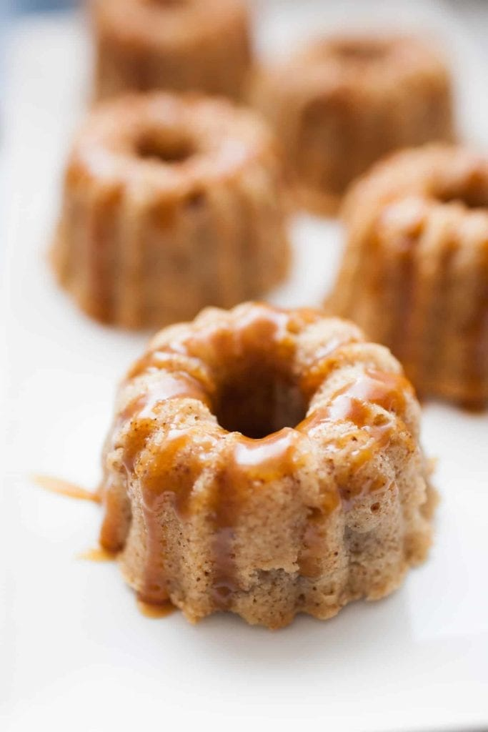 Mini bundt shaped cakes sitting on a white serving platter covered in homemade caramel sauce.