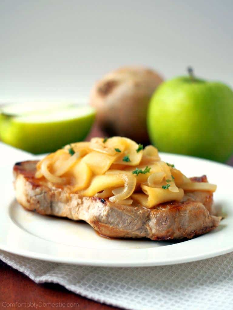 An Apple Cider Pork Chop sits on a white plate with apples in the background