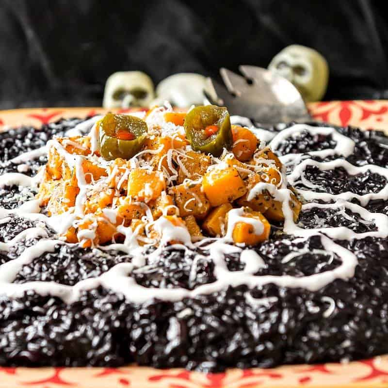 A platter of Black Rice Risotto with Butternut Squash is decorated in a Halloween manner