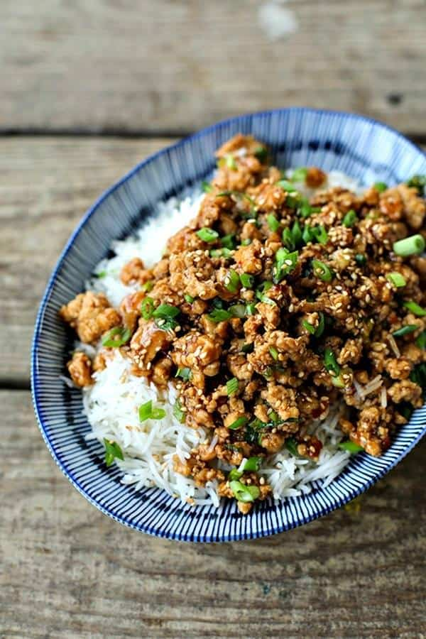 A blue bowl holds Cheater Sesame Chicken over white rice on a wooden background
