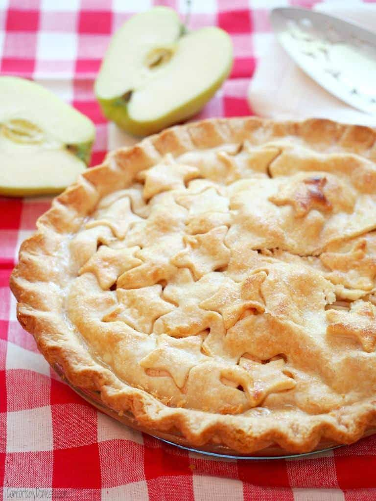 A whole Classic Apple Pie sits on a red checkered tablecloth