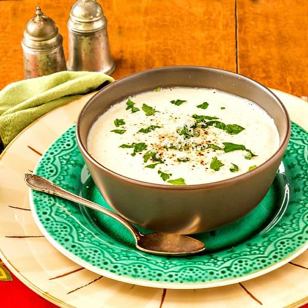 A bowl of Cream of Cauliflower Soup sits on a green platter with a spoon, ready for eating