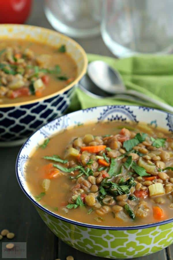 Two bowls of Lentil Soup sit on a green napkin with spoons