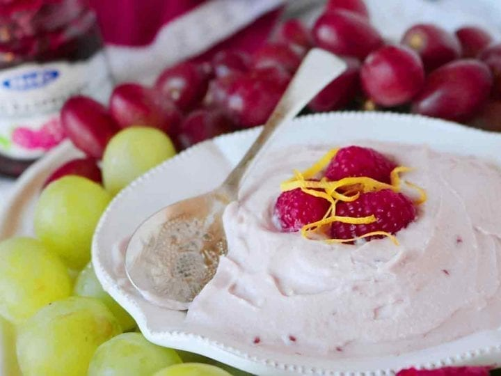 A bowl of Raspberry Yogurt Fruit Dip is served with a spoon and various fruits