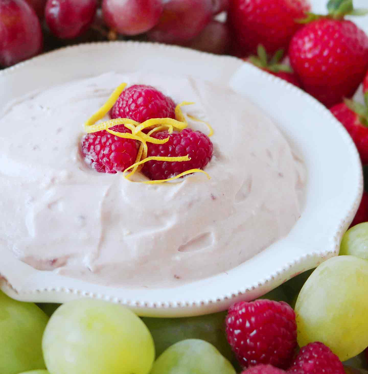 A bowl of Raspberry Yogurt Fruit Dip is served with green grapes, red grapes, fresh raspberries and strawberries