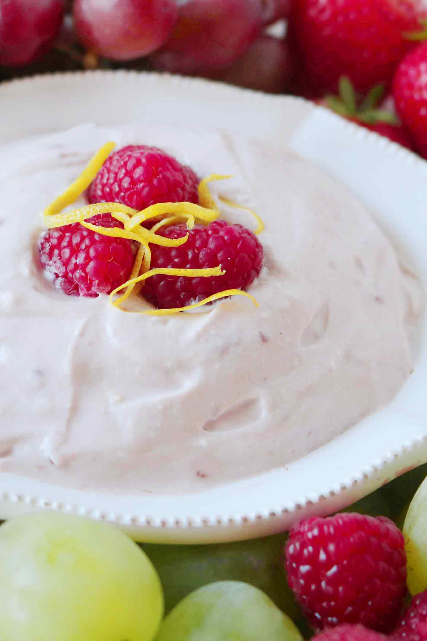 Close up of Raspberry Yogurt Fruit Dip, garnished with fresh raspberries and lemon zest