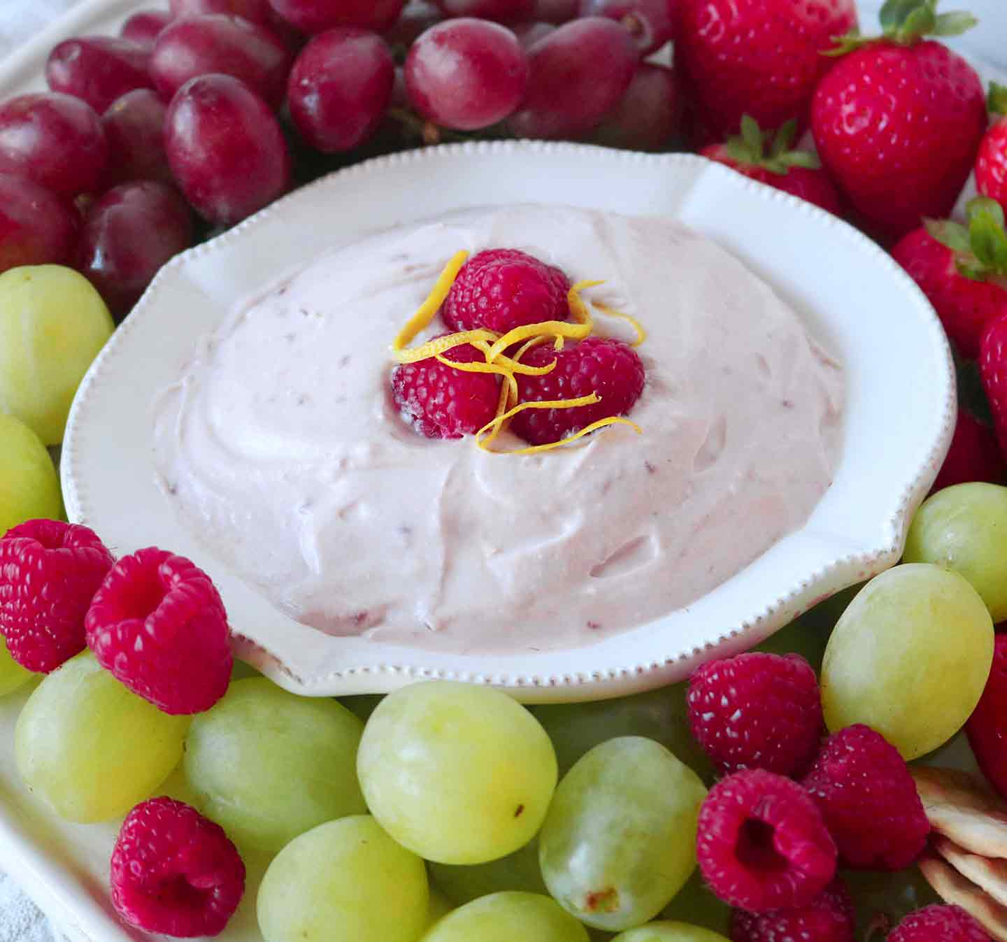 Raspberry Yogurt Fruit Dip is served with fresh raspberries, green and red grapes