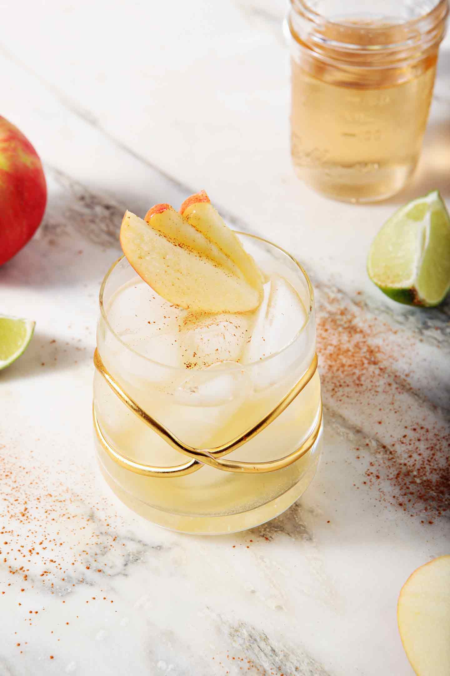 A Apple Pie Moscow Mule sits on a marble background, surrounded by apples and lime slices