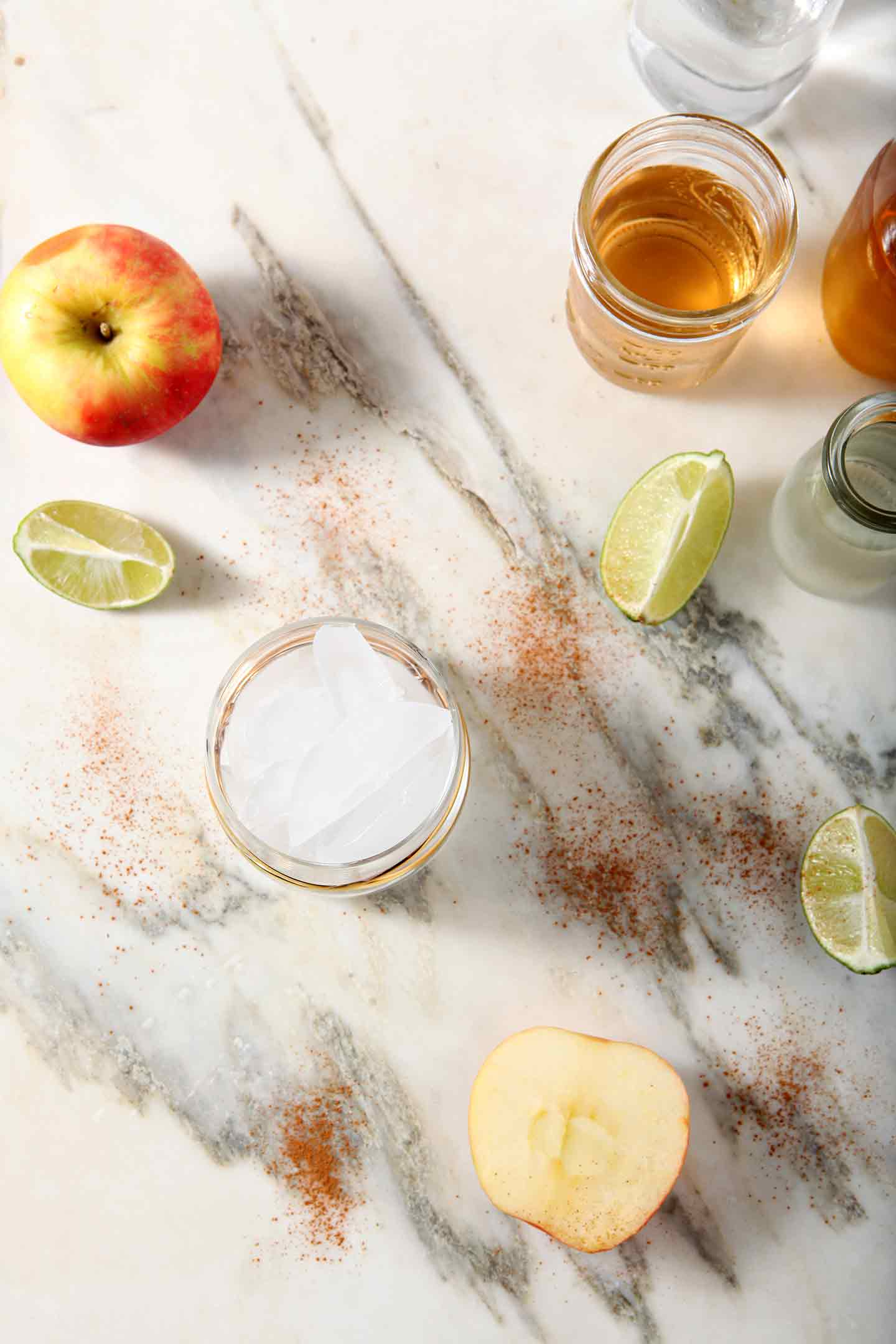 Ingredients for Apple Pie Moscow Mules are lined up on a marble backdrop
