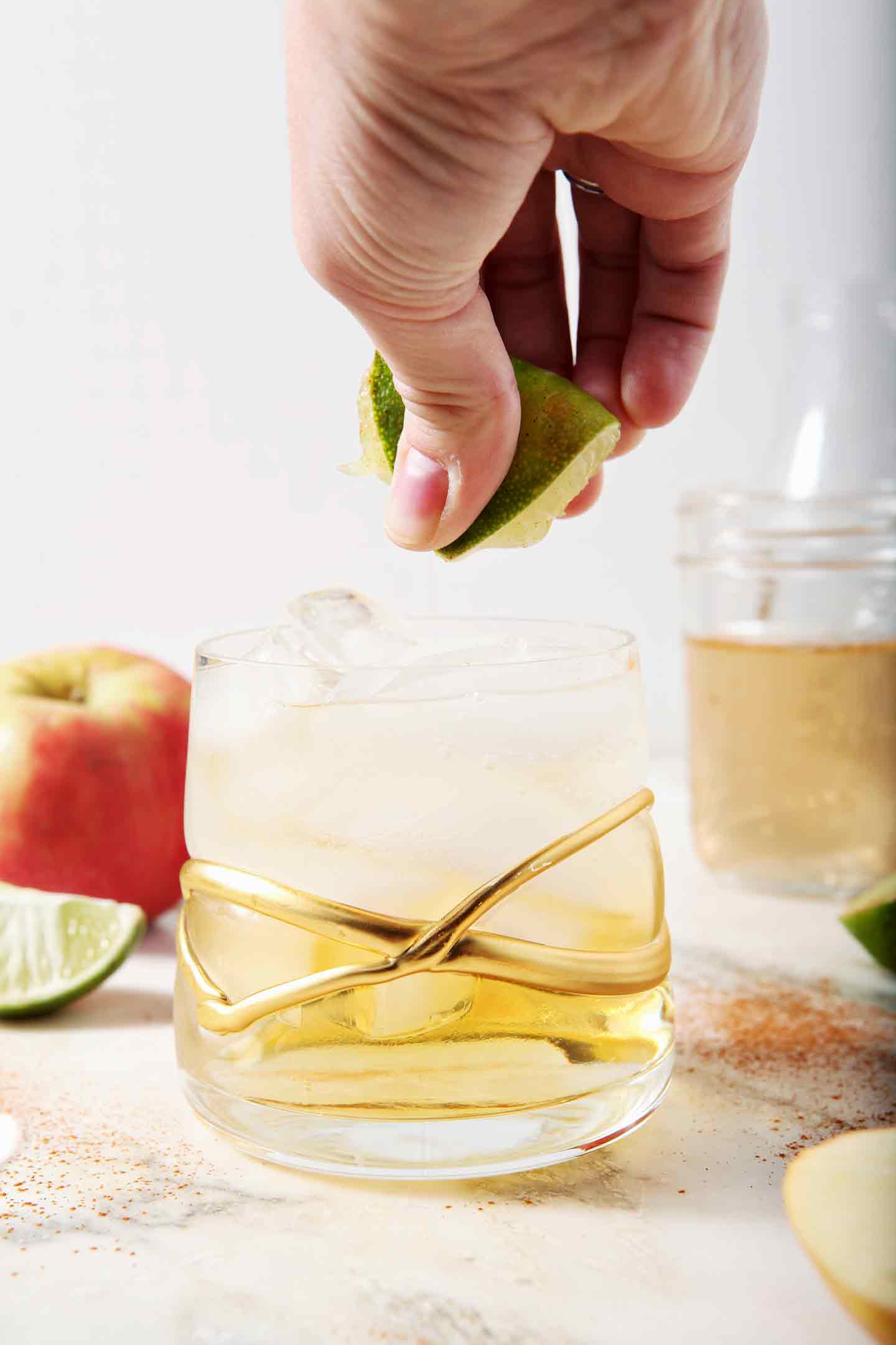 A lime is squeezed into a newly mixed Apple Pie Moscow Mule