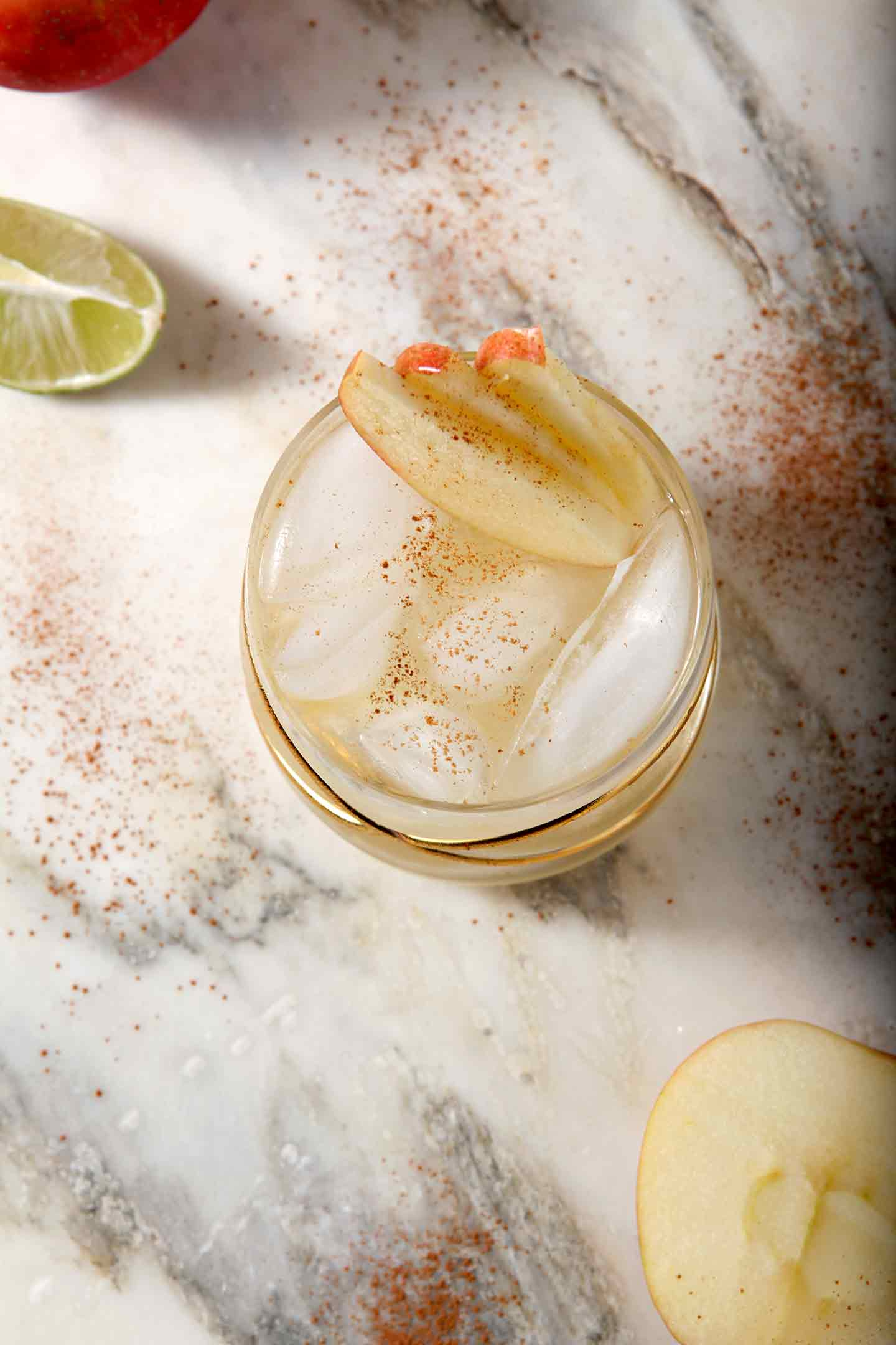 Overhead image of a Apple Pie Moscow Mule, shown with apples and lime slices