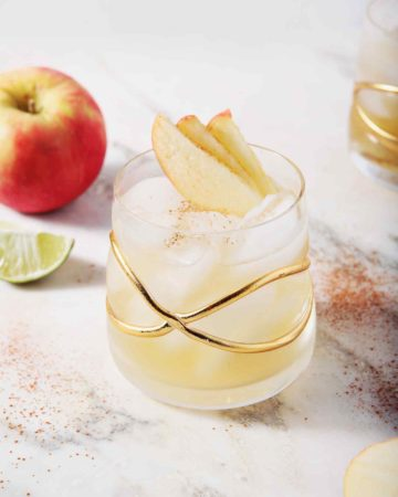Two Apple Cider Moscow Mules sit on a marble background, surrounded by apples, lime slices and cinnamon