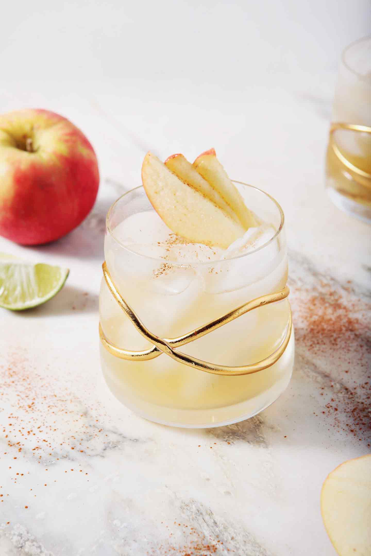 Two Apple Pie Moscow Mules sit on a marble background, surrounded by apples, lime slices and cinnamon