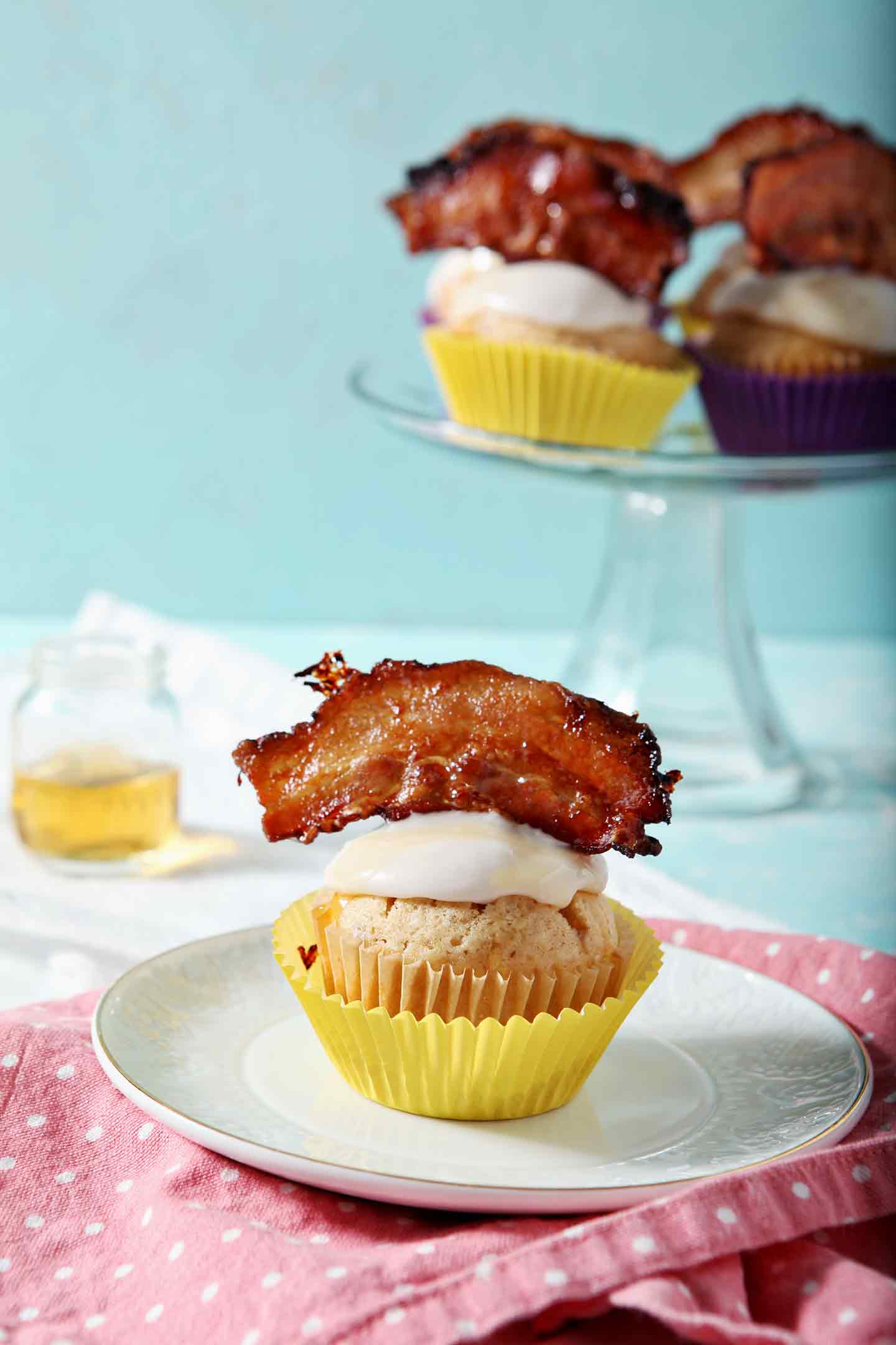 A Bourbon Maple Bacon Cupcake sits on a small plate, garnished with Maple Bacon, and ready for eating