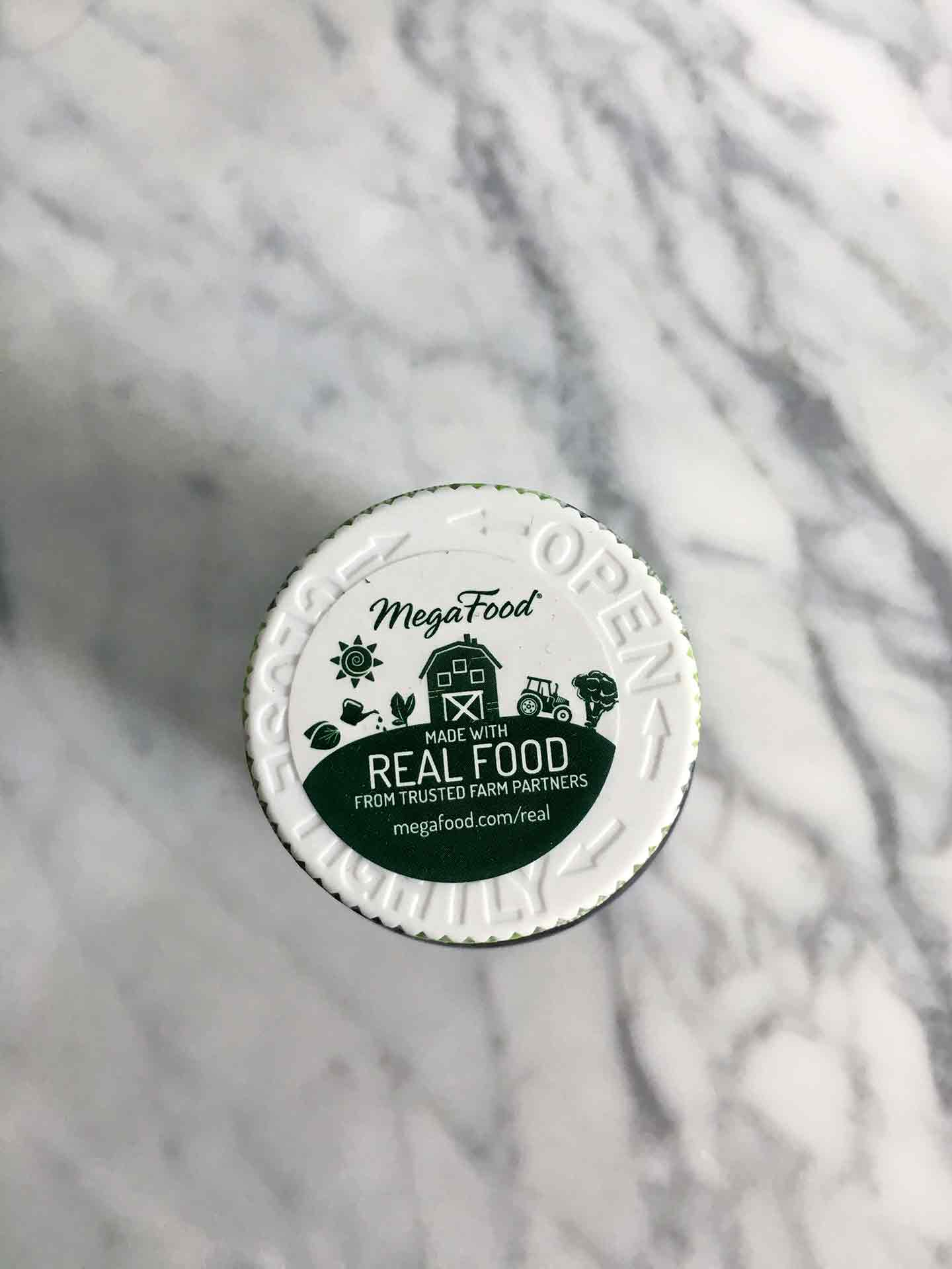 A jar of MegaFood sits on a marble background, touting Real Food ingredients