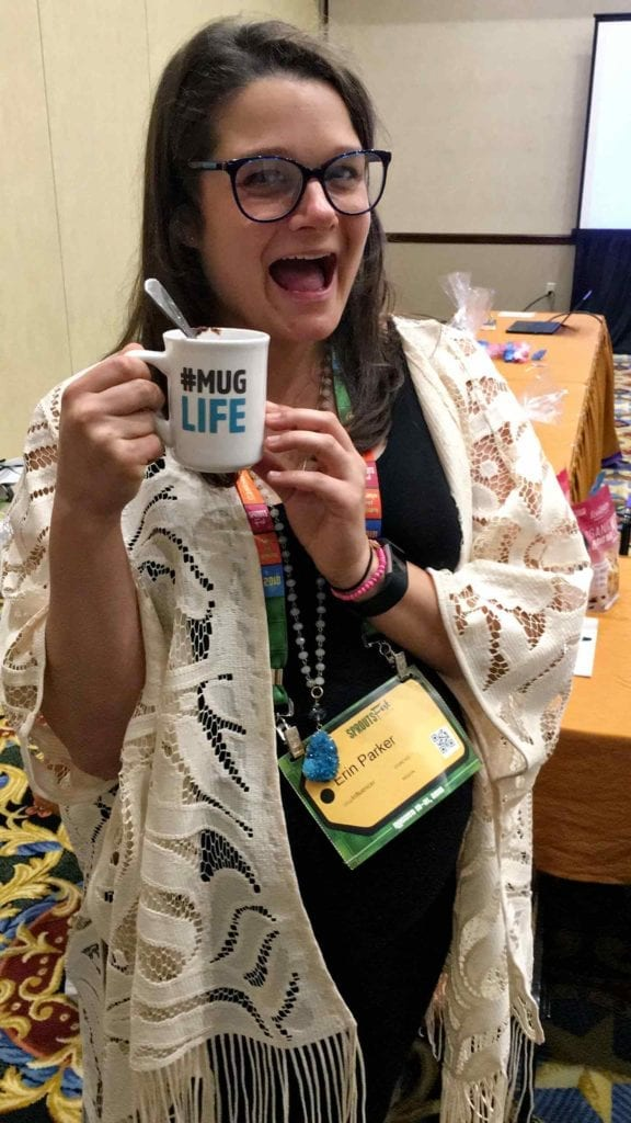 Erin Parker holds a #MugLife cup with a FoodStirs mug cake inside at SproutsFest