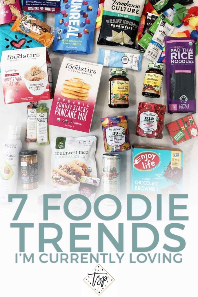 Pinterest image for 7 Foodie Trends I'm Loving 2018, featuring an overhead of some of the products brought home from SproutsFest on a white background