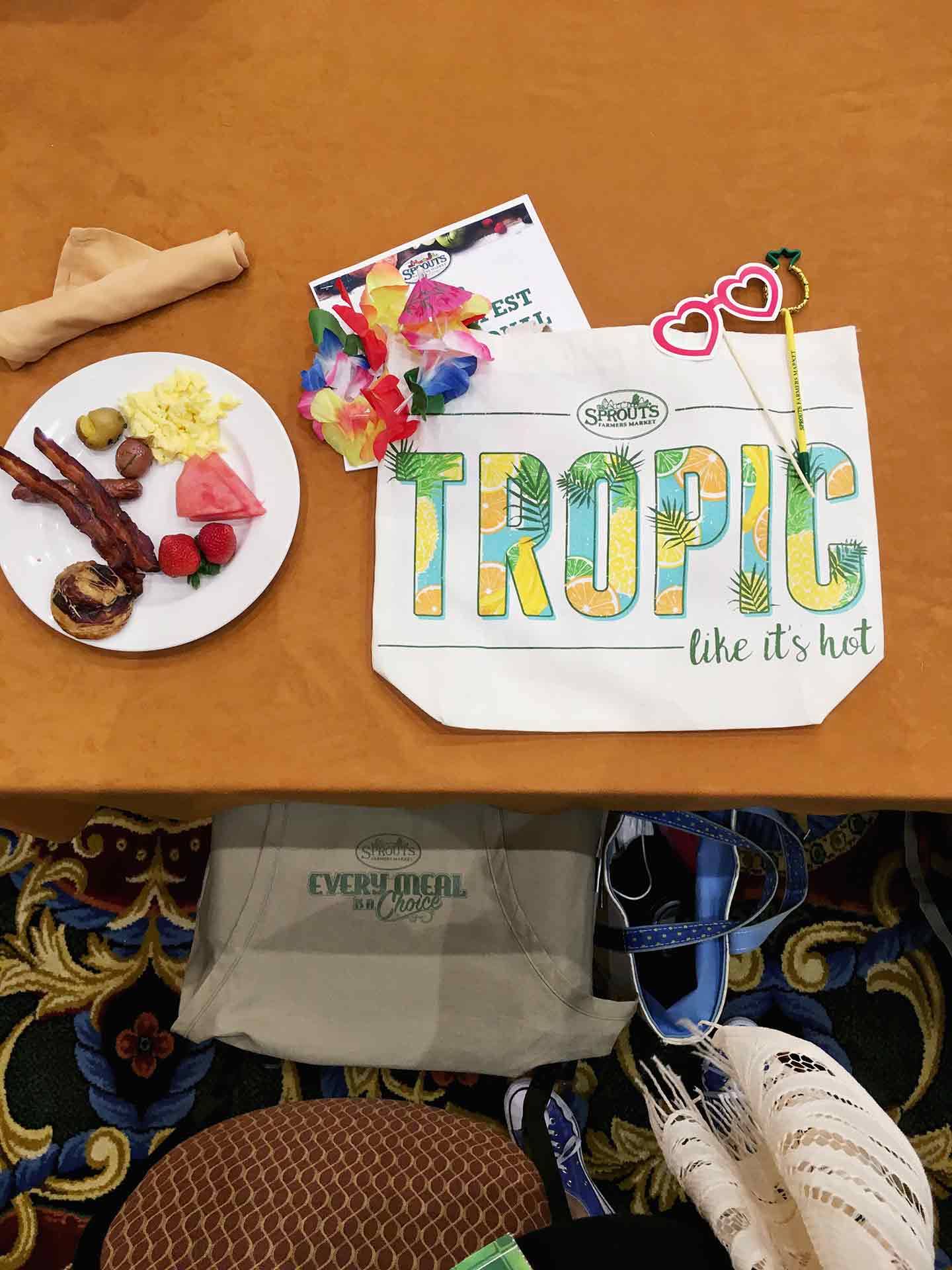 A canvas reusable bag sits on a table with breakfast at SproutsFest