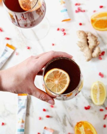 A woman grabs a Pomegranate Ginger Orange Sparkling Mocktail from a marble background
