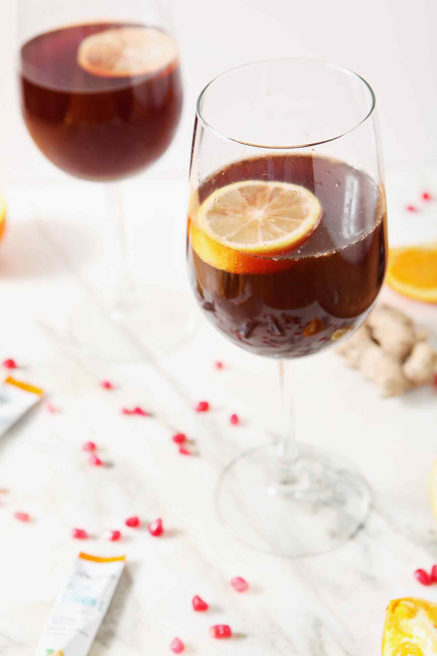 Two Pomegranate Ginger Orange Sparkling Mocktails, garnished with lemon slices, are shown on a marble background, surrounded by fresh ginger root, pomegranate arils and orange slices