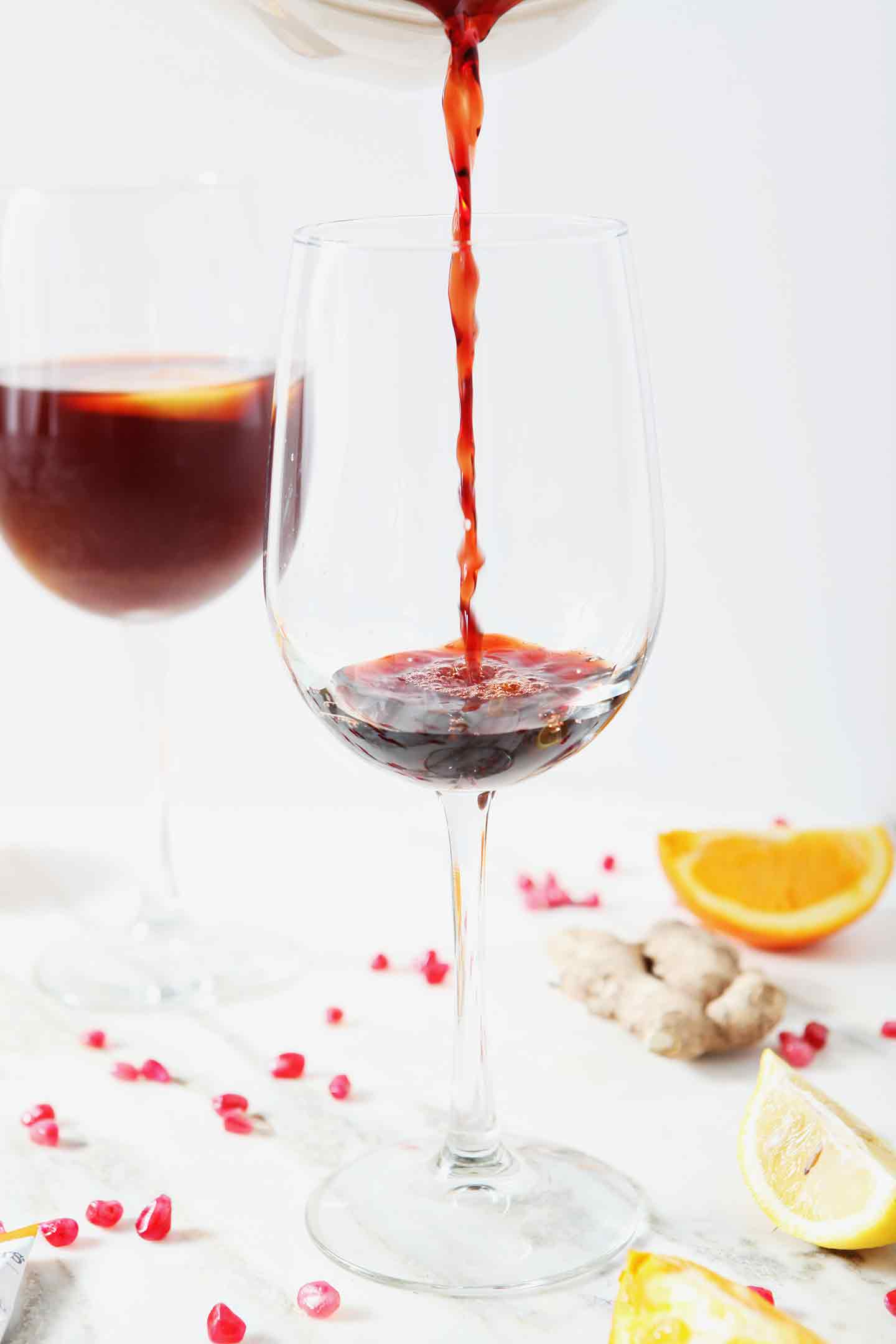 Pomegranate juice is poured into a wine glass to begin making a Pomegranate Ginger Orange Sparkling Mocktail
