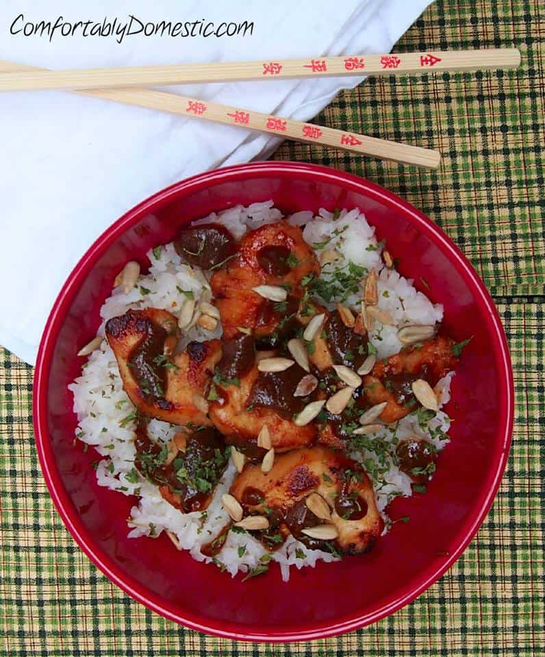 A red bowl of {Nut Free!} Chicken Satay with Coconut Rice sits on a plaid background with chopsticks