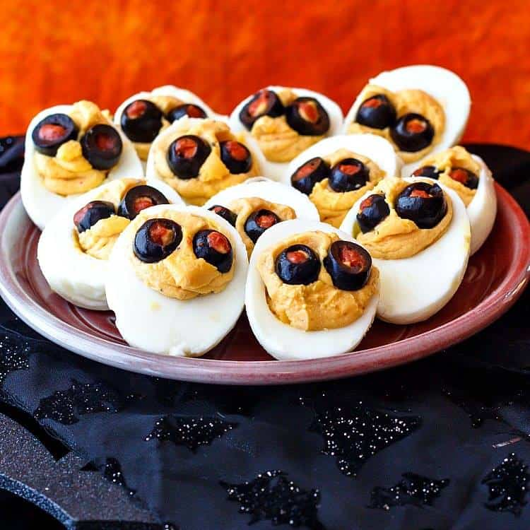 A platter of Halloween Deviled Eggs sits on a black and orange background