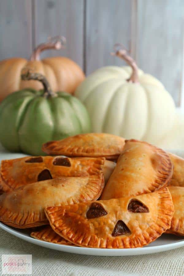 A plate of orange Pumpkin Empanadas with cut-out faces sit in front of three pumpkins