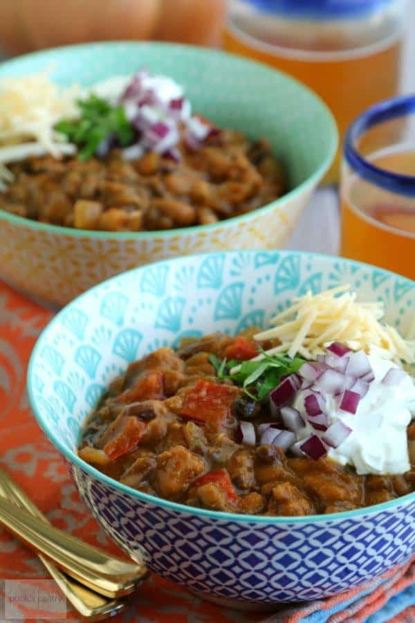 Two bowls of Slow Cooker Chipotle Turkey Pumpkin Chili sit on an orange tablecloth with drinks