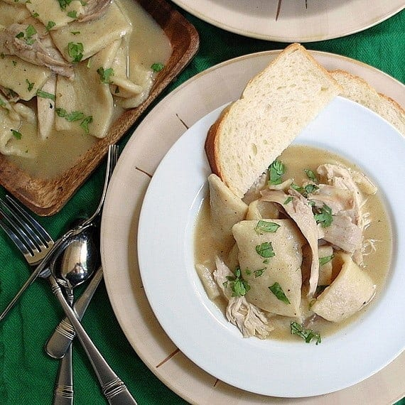 A bowl of Southern Chicken & Dumplings sits on a green tablecloth