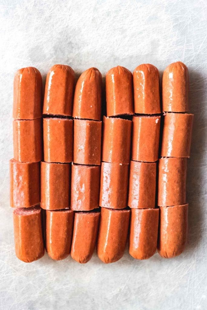 Cut hot dogs are lined up, ready to be placed into the biscuits