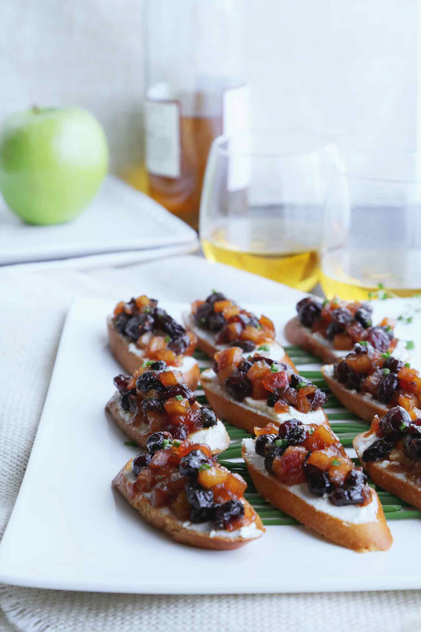 Apple Chutney Bruschetta line a white plate, served with glasses of white wine.