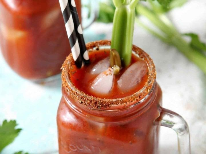 Two BBQ Bloody Marys are garnished with pickled green beans and fresh celery sticks