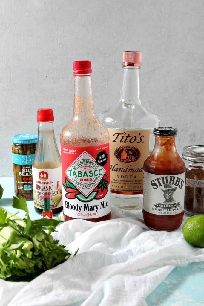 Ingredients for BBQ Bloody Mary sit on a turquoise background