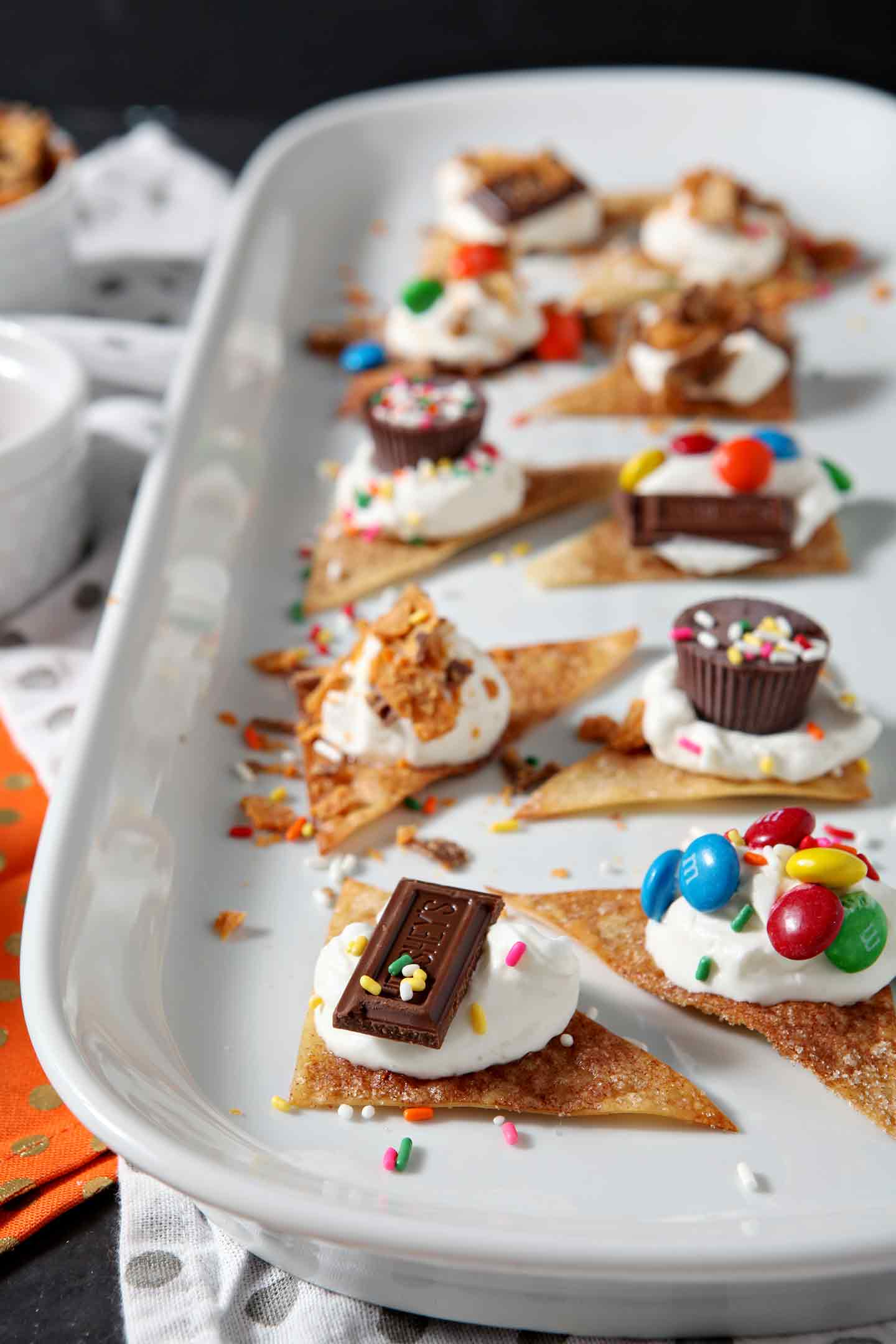 Individual Halloween Dessert Nachos line a long platter, surrounded by additional candy and whipped cream