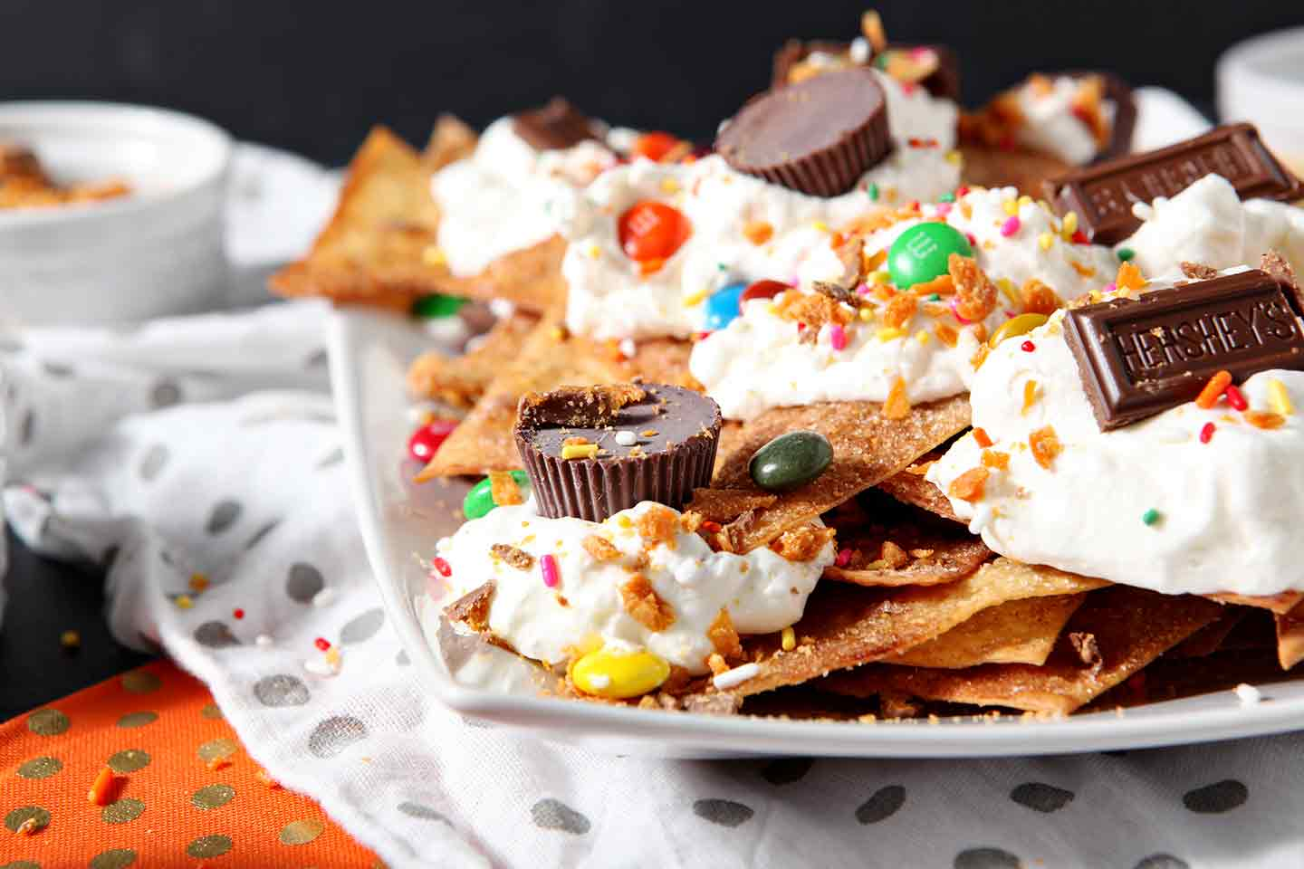 Horizontal image of a platter of Halloween Dessert Nachos, featuring several types of Halloween candy