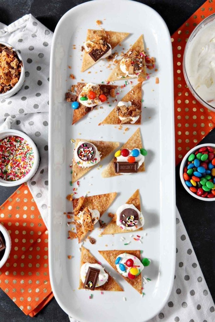 Individually decorated dessert nachos from above on a platter, surrounded by candy