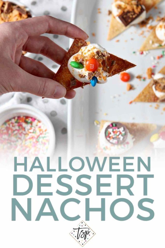 Pinterest image for Halloween Dessert Nachos, featuring a woman holding an individual nacho from above with Pinterest text