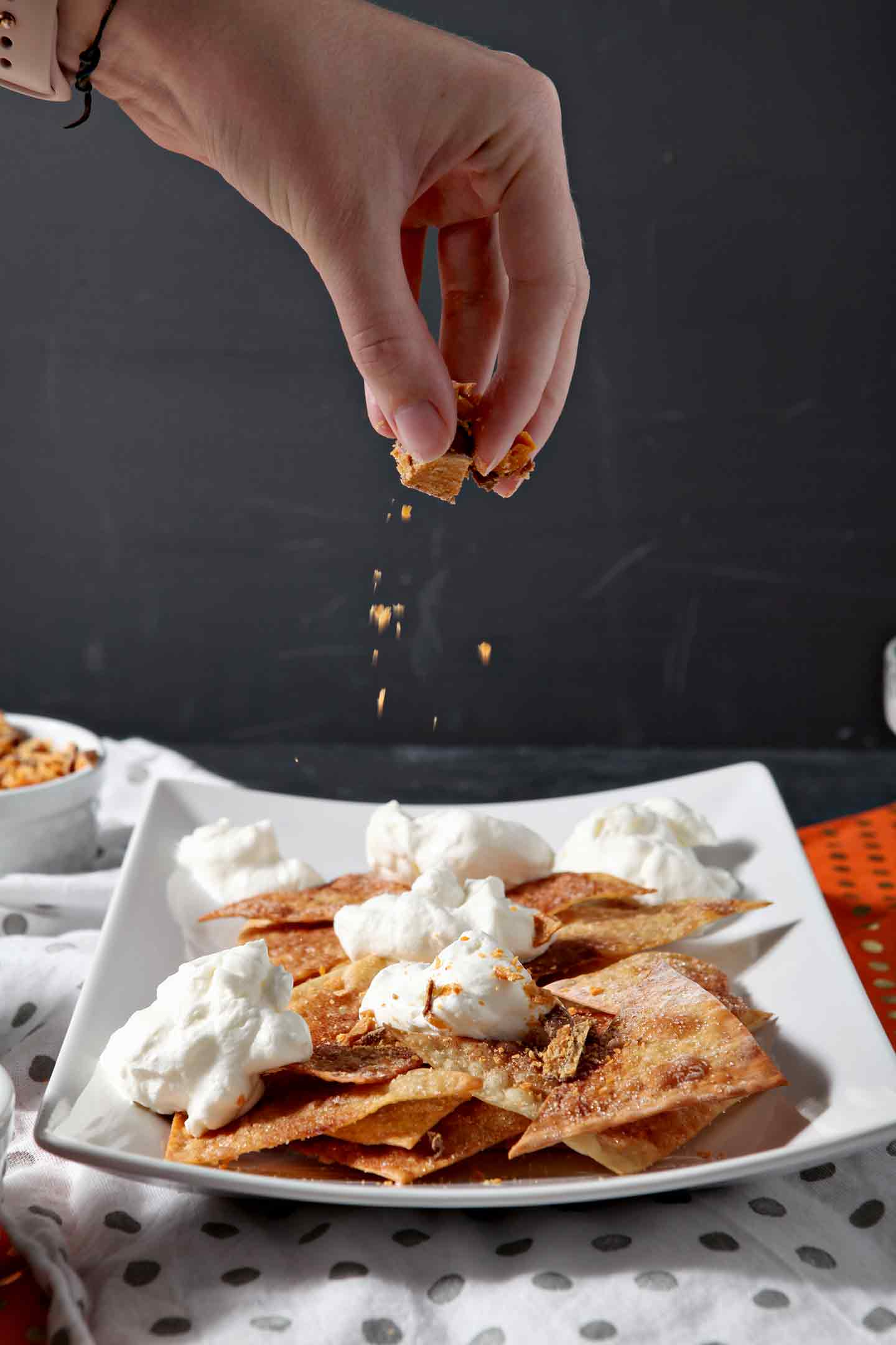 Butterfingers are sprinkled on top of a platter of crispy wontons with whipped cream before other toppings are added