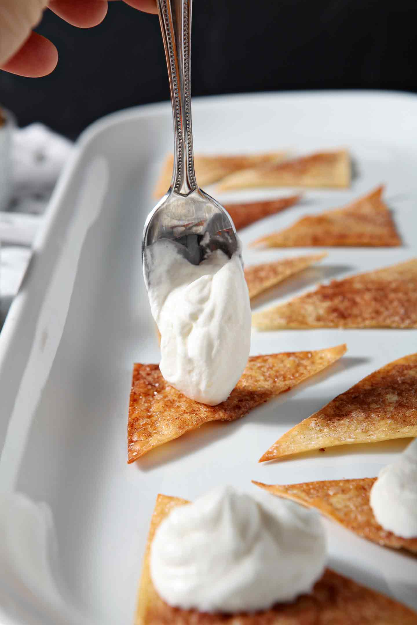 Sweetened whipped cream is dolloped onto Cinnamon-Sugar Wonton Chips to make the base for Halloween Dessert Nachos