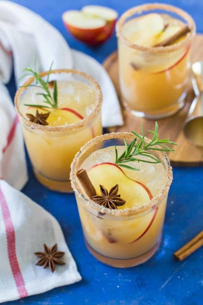 Three Apple Cider Margaritas, garnished with apple slices, cinnamon sticks, star anise and sprigs of rosemary, are served on a blue background